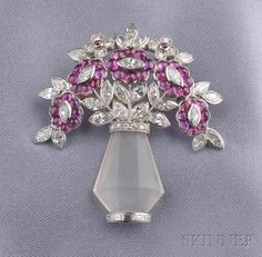 Art Deco Platinum, Rock Crystal, Ruby, and Diamond Brooch, designed as a rock crystal vase with arrangement of buff-top ruby flowers, marquise-cut diamond leaves and diamond melee florets, millegrain accents, lg. 1 5/8 in.