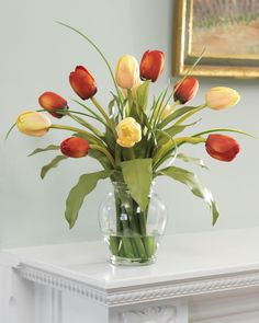 A pleasing combination of exuberance and gentility, these silk tulips make delightful accents. In pink and white or red and yellow, the lifelike petals rest amid sprigs of grass in our hiqh quality glass vase.