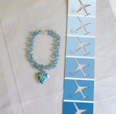 Chainmaille & blue glass beads make a simple bracelet with a single heart shaped charm in shades of blue and green.