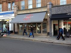 This Victorian Shop Blind adds character to any shop front, compared to next door with a modern awning by Deans Blinds And Awnings