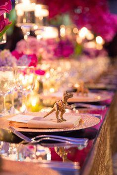 Gold Tyrannosaurus rex figurines stood at each place setting. #placesetting #dinosaur #figurine Photography: Ira Lippke Studios. Read More: http://www.insideweddings.com/weddings/dinosaur-chic-celebration-at-the-american-museum-of-natural-history/571/
