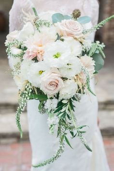 Cascading peach and white wedding bouquet with hints of mint and forest green.