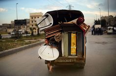 And here, a boy holds a satellite antenna as he travels on the back of a truck in Aleppo – 1.3 million people have so far fled Syria to neighbouring countries since the beginning of the conflict