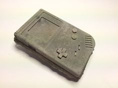 First seen around 1989, this Dexteludicrum repuerasco (or Game Boy) has  been found throughout the world. The Dexteludicrum obviously shares some of  the same traits as Dominaludus, but includes some extra components.    (This piece is hand-cast in a special blend of concrete. Slight variations  in color and surface detail may occur.)