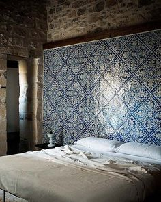 Ever thought of tiling your bedroom? We love the use of these Moroccan tiles above this bed in this rustic Italian bedroom.