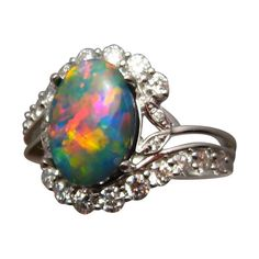 A stunning Black Opal ring with Diamonds in 14k Gold with an oval Lightning Ridge Black Opal accented with 2 mm bright white Diamonds.