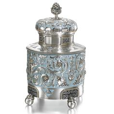 A FABERGÉ SILVER AND ENAMEL TEA CADDY, MOSCOW, 1908-1917 cylindrical, the sides and dome lid cast with swirling Art Nouveau foliage on a pale blue matte enamel ground, the parcel-gilt borders with geometric motifs, the base with purple enamel reserves above four ball feet, silver-gilt and cork stopper, all three components with K. Fabergé in Cyrillic beneath the Imperial Warrant, scratched inventory number 18719, 88 standard