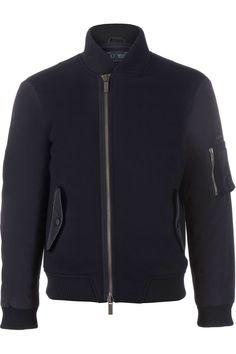 Blauwe jas van het merk Armani Jeans. De jas heeft een voorpand welke van een andere stof is dan de mouwen. Op de linker mouw zit een zakje en voorop twee zakken welke sluiten met een druk knoop.