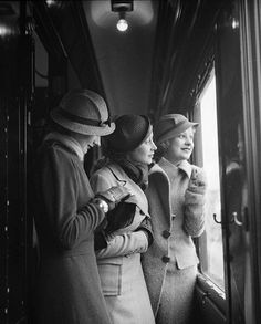 Huddled together in a train carriage corridor, they watch for their station's approach through the window. Their ensembles reflect the clipped elegance of 1934. Boris Lipnitzki shows us each detail.