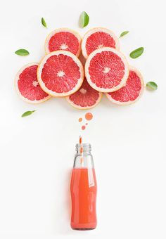 Grapefruit juice in bottle with thinking bubbles formed by slice of grapefruit.