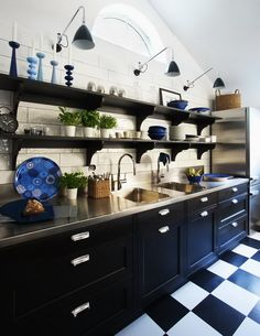 dark grout - white tile wall + pendant sconces + open shelving + stainless steel counter + black cabinets + checkered floor in kitchen via nicety journal