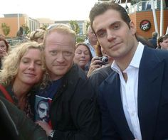"""FLASHBACK FAN PIC  This is a fun one.  Darren posted this picture of him and his fiance, Adele, with Henry at the Jersey Man of Steel premiere.  Darren has a great sense of humor and shared this.  """"Adele is clearly in dreamland about being with Superman.""""  He continued, """"Henry Cavill was there, too.""""  Two Superman in one photo.  She is a lucky lady.  Awesome picture!"""