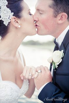 Kissing with rings locked together.  Photo by I Heart Weddings