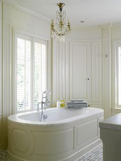 Best of Both Worlds:  Combining the style of a tub surround with the structure of a freestanding tub creates a unique look that gives this bathtub presence. The beautifully detailed wood surround wraps around the oval tub and is topped with a ledge of elegant marble, encasing the freestanding tub.