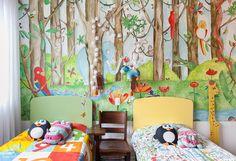 Quarto infantil tem papel de parede com estampa de floresta e camas com cabeceira colorida.