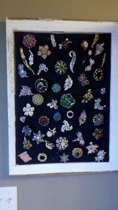 Neat way to display antique broaches on fabric covered foam board mounted on to the glass of an old window frame.  Love!