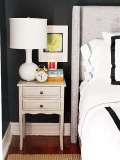 """The Everygirl's """"How to Style"""" Sale on Joss and Main - nightstand, black walls, grey tufted headboard"""