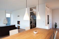 Haus L. - Essbereich mit Blick auf den Kamin, Küche und Flurtüre aus Glas - stkn architekten