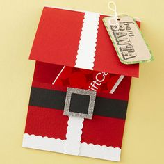 GC holder -  Gatefold a piece of red cardstock to create the pocket, then adhere strips of scallop-edge white cardstock, referring to the photo for placement.  To make the belt, adhere a strip of black cardstock to the lower half of the card and punch a square from glittery cardstock. Attach the square shape to the black strip. Tuck your gift inside the card.  Wrap white embroidery thread around the top flap twice and secure with a dab of glue in the back. Tie on a die-cut gift tag. - bjl