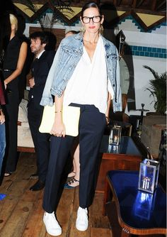 Jenna Lyons in a denim jacket + white button-up + navy trousers + white sneakers