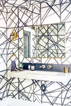 Black and white wallpaper in bathroom with gold accents