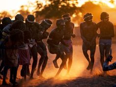 Aboriginal Dancers    Photograph by Penny Tweedie/Getty Images    Aborigines kick up dust in a dance at sunset. The original inhabitants of Australia, Aborigines were there for more than 40,000 years before white men arrived. European settlers brought disease and politics to the continent, severely endangering the Aborigines' distinct culture, language, and lifestyle.