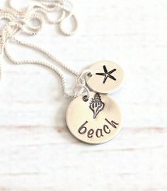 Beach lovers jewelry. A seashell with the word beach has been hand stamped on a sterling silver disc and is complimented by a tiny silver.