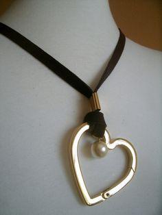 Colar com fita de couro marrom (ou preta) e coração banhado a ouro( de primeira linha, não escurece.) e detalhe em pérola.  Ajustável. Enfia pela cabeça e pode ser usado no comprimento desejado. R$ 130,00