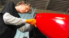 "Edd China tinkers around with a red sportscar in the ""Wheeler Dealers"" garage (DiscoveryUK)"