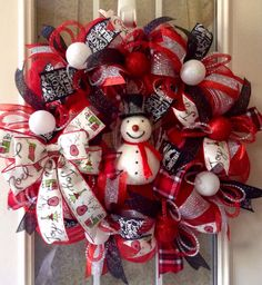 This is a 24 wreath made from red deco mesh. It is wrapped in silver deco mesh. Coordinating plaid flannel, black chalkboard, black glitter mesh, cream/red, and red and silver striped glitter ribbons. Ribbon centers are accented by silver and red deco mesh tubing and red or white ornament. Center is decorated with 8 x 5 snowy glittered snowman. Attached ribbon for hanging.