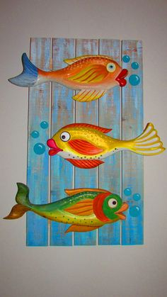 Carved and painted fishes on a distressed wood board.