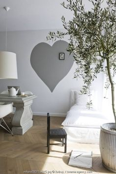 Love this idea. Paint a heart on the wall and fill it with frames.