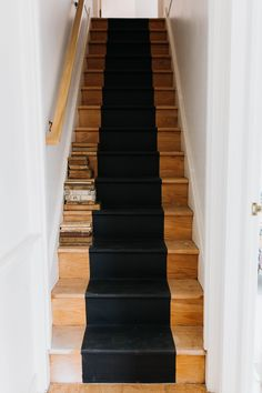 narrow wood stairs with black stripe down the center