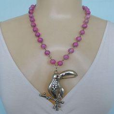 Colar feito com contas acrílicas rosa e um pingente tucano prateado com strass. R$ 15,00