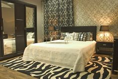 Master bedroom with patterned wallpaper and zebra area rug.