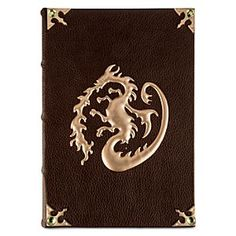 Disney Descendants Journal | Disney StoreDescendants Journal - A golden fire-breathing dragon guards the contents of this Descendants Journal. The faux leather binding is accented with rhinestone-studded metal corners, while the lined pages within feature entwined dragons and space for your spells.