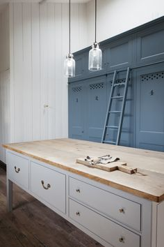 Numbered blue kitchen cabinets and a roilling ladder in a Dorset farmhouse kitchen by Plain English