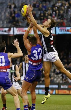 Darcy Moore marks over the top of Bulldogs defender Michael Talia. Collingwood Football Club, Western Bulldogs, Men In Uniform, Sport Man, Rugby, My Boys, Goals, Drawing Reference, Acrylic Nails