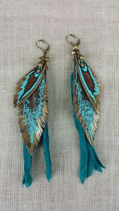 Take off to an island in the Caribbean Sea and dance the night away with these beautiful earrings showing off your FREE SPIRIT. The teal and turquoise pop off of the brown leather feathers. Add sparkl