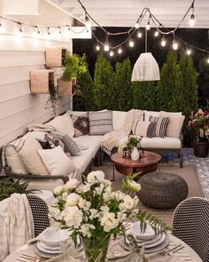 Bunch of pillows and and cozy cushion seats with the touch of green make this patio beautiful and inviting.
