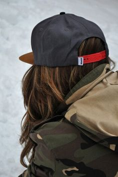 The female Nico. Camo jacket, brown hair, and a cap.