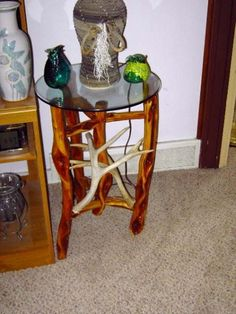 A glass table top end table with diamond willow legs and mule deer horns.