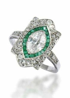 AN EARLY 20TH CENTURY EMERALD AND DIAMOND RING  The central marquise-cut diamond to a calibré emerald border and pavé-set diamond shield shaped surround, raised on a scrolling gallery, to diamond-set shoulders and a plain hoop, circa 1915
