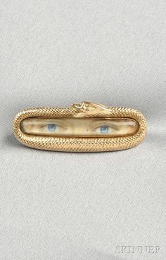 ANTIQUE LOVERS EYE BROOCH, DEPICTING A PAIR OF BLUE EYES WITHIN A GOLD FRAME DESIGNED AS A SERPENT SWALLOWING ITS TAIL, LG. 1 3/8 IN - Skinner Inc