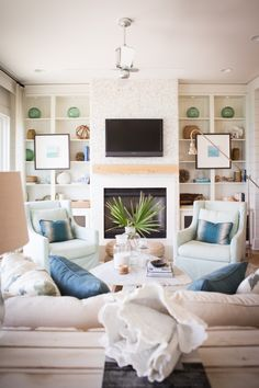 Ashley Gilbreath, styled built-in bookcases, art on bookcases, pair of chairs, comfy sofa, beachhouse style