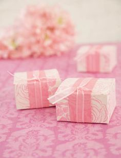 Michaels.com Wedding Department: Romantic Pink Stamped Favor Boxes These romantic rose favor boxes are sure to please the senses. An ivory favor box has no bound when paired with stamps and a soft palette of inks, paper and ribbon. Select your favorite soft hue from many papers and inks in Michaels scrapbooking department. Stamp the favor box and also the paper band to create a monochromatic look. Soften it all with an airy satin edge ribbon. Courtesy of Gartner Studios®