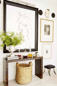 White walls, with black and white gallery wall, brown bar table, and large woven basket