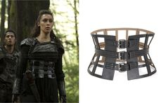 "Lexa (Alycia Debnam Carey) wears a BCBGMAXAZRIA Grid Cutout Corset Waist Belt in the color Black in The 100 Season 2 Episode 10 ""Survival of the Fittest."""