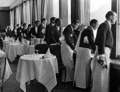 Waiters in the Grand Hotel dining hall watching Sonja Henie ice skating, St Moritz [Switzerland] 1932, photo by Alfred Eisenstaedt