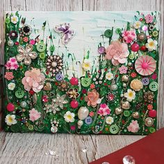 This is a mixed media canvas of a flower meadow. It is a mixture of glitter and acrylic paint with vintage jewellery, buttons, beads and rhinestones. The canvas measures approx 20x25cm so is perfect to either hang or have on a shelf or fireplace - it would be a great addition to any